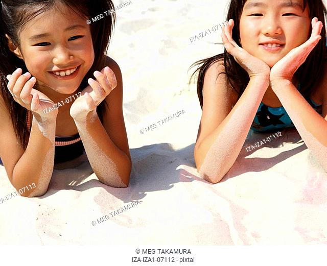 Close-up of two girls lying on the beach and smiling