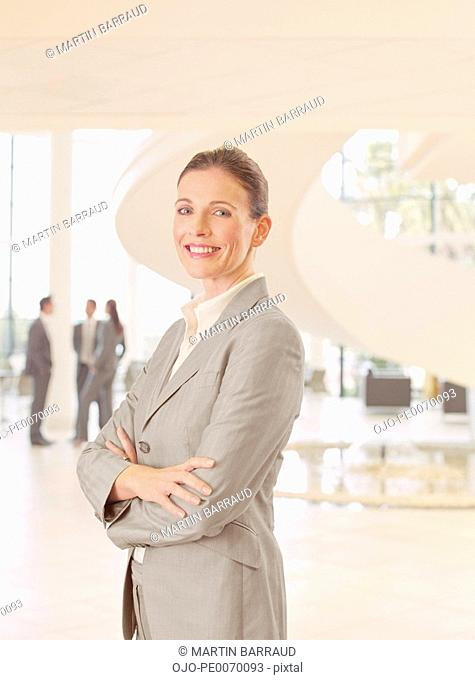 Businesswoman standing with arms crossed in lobby