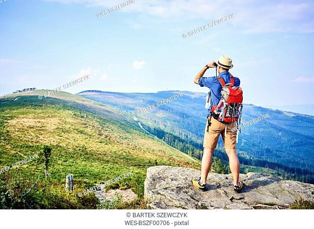 Rear view of man looking through binoculars during hiking trip