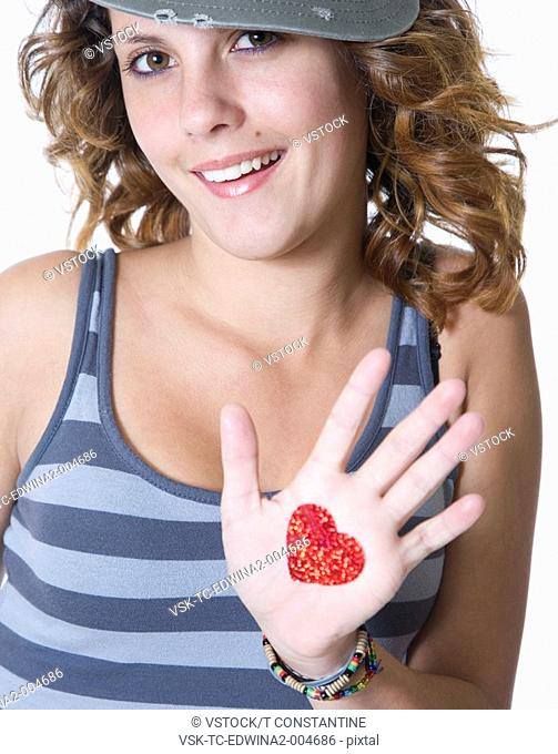 Studio portrait of smiling teenage girl 14-15 with heart drawn on hand