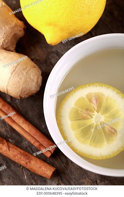Cup of ginger tea and fresh ingredients - ginger, cinnamon and lemon