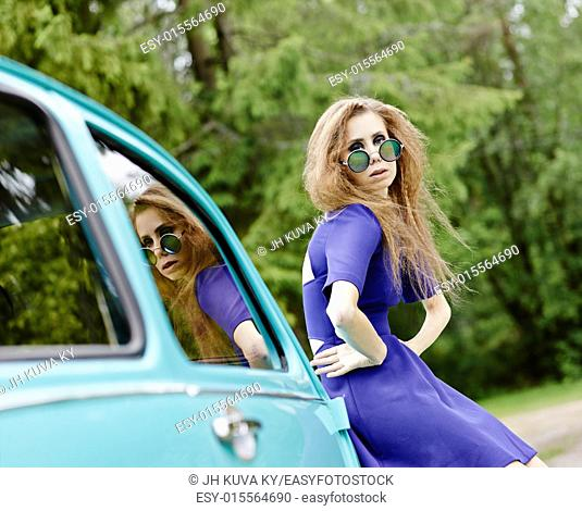 Close up, beautiful hippie girl wearing a mirrored sunglasses and leans against a car, cross processed retro effect