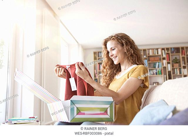 Smiling woman at home sitting on couch unpacking parcel with garment