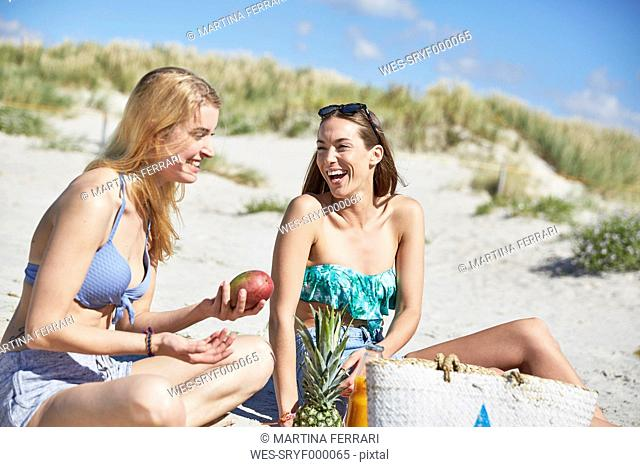 Two female friends on the beach enjoying healthy snack