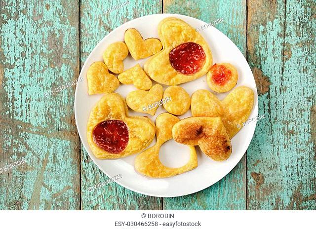 Homemade puff hearts cookies decorated with jam on white plate flat lay overhead view