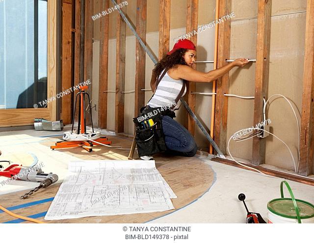Hispanic woman wiring construction site