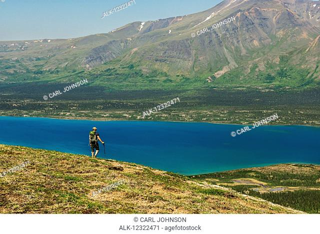 A hiker looks out over Twin Lakes from a mountain ridge in Lake Clark National Park & Preserve, Southcentral Alaska, USA