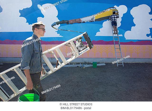 Artist carrying ladder near mural wall