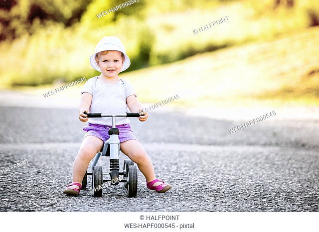 Portrait of smiling toddler girl sitting on bobby car