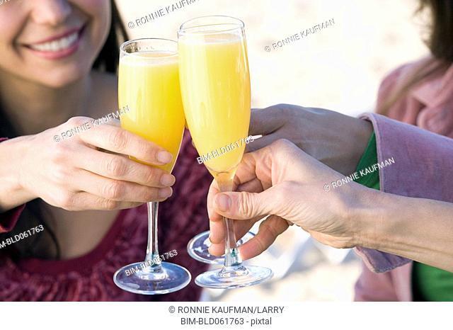 Multi-ethnic women toasting with mimosas