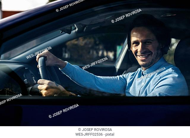 Portrait of smiling businessman driving car