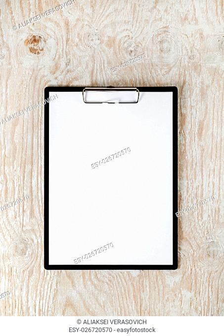 Photo of clipboard with a blank sheet of paper on light wooden background with plenty of copy space. Blank template for design presentations and portfolios