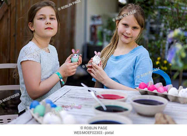 Portrait of two girls decorating Easter eggs on garden table