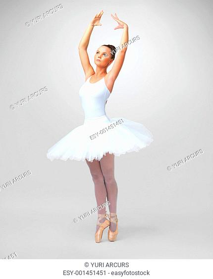Full length of a beautiful young ballerina dancing against white background - copyspace