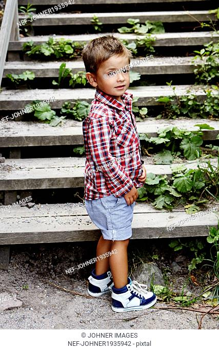 Boy standing, stairs in background, Stockholm, Sweden