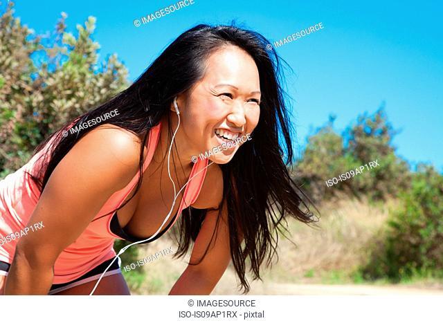 Mid adult woman in sports clothing, wearing earphones, looking straight ahead
