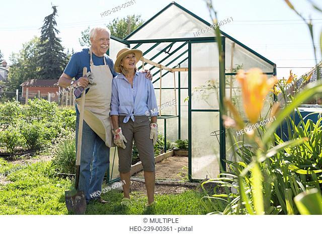 Senior couple with shovel at garden greenhouse