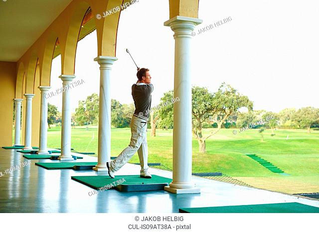 Golfer in archways practising golf swing looking away