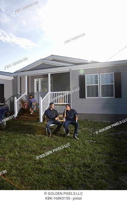 Blue-collar men sitting and talking in front yard of trailer home