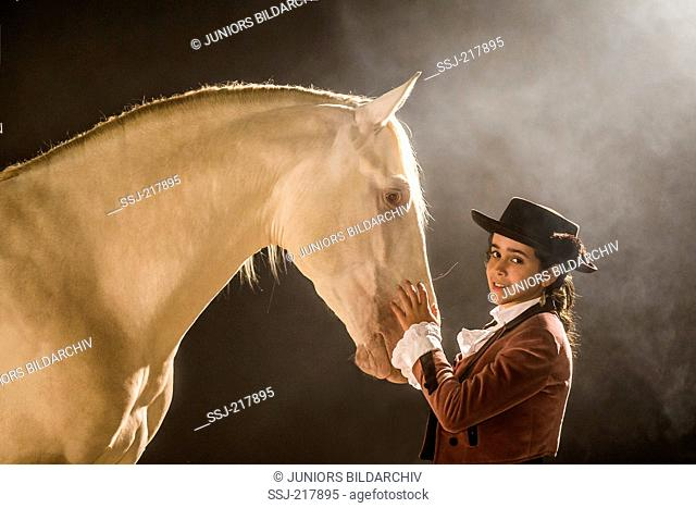 Lusitano. Girl in traditional dress fondling a cremello gelding at night. Portugal