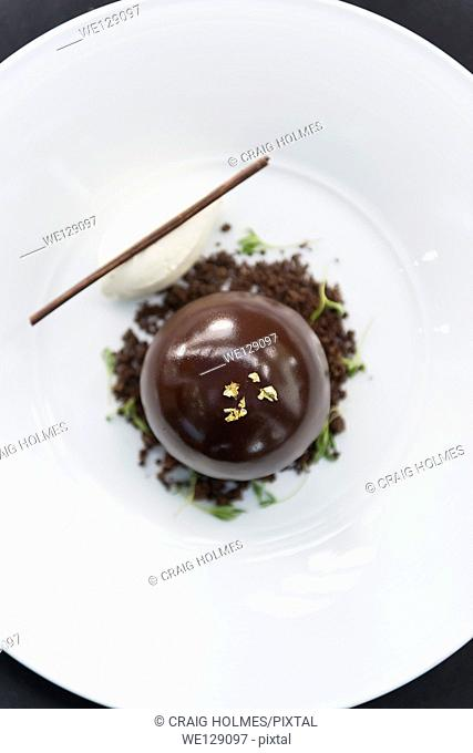 Chocolate bombe dessert served with vanilla ice cream