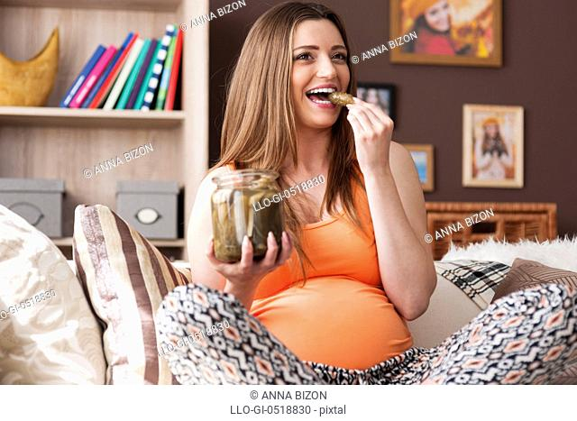 Pregnant beautiful woman eating pickles. Debica, Poland