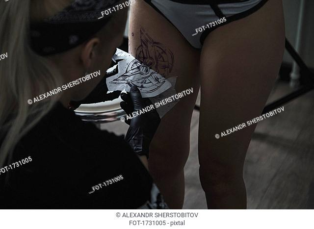 Artist peeling off tattoo stencil on female customer's thigh at studio
