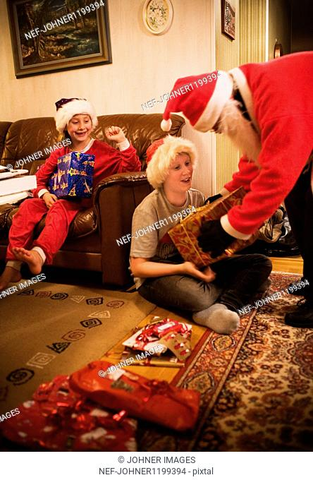 Santa Claus giving presents to children in room