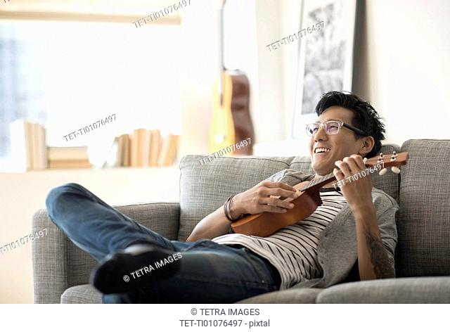 Man sitting on sofa and playing ukulele
