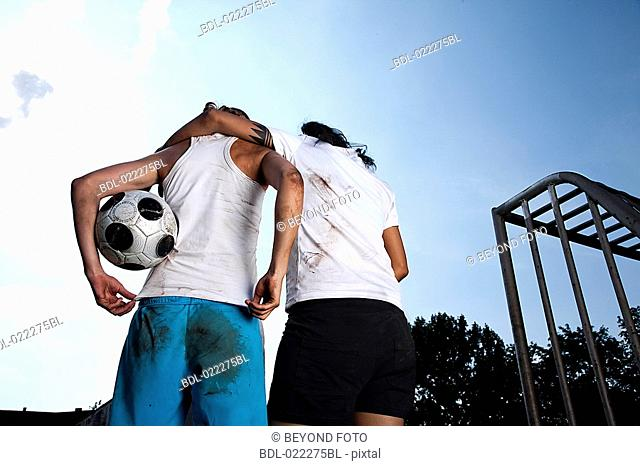 rear view of two female football players embracing