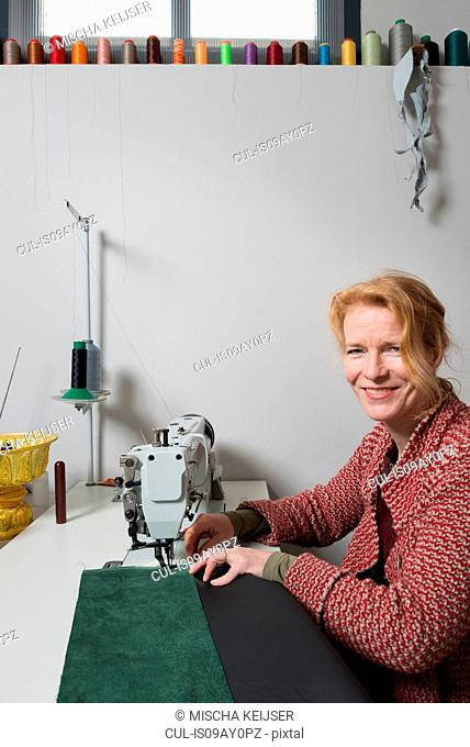 Woman at sewing machine looking at camera smiling