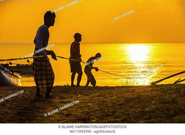 Fishermen haul in a fishing line at sunrise, Kinniya (near Trincomalee), Eastern Province, Sri Lanka