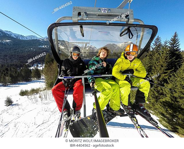 Three teenagers on chairlift with skis and snowboard, taking selfie, Spitzingsee ski resort, Bavaria, Germany