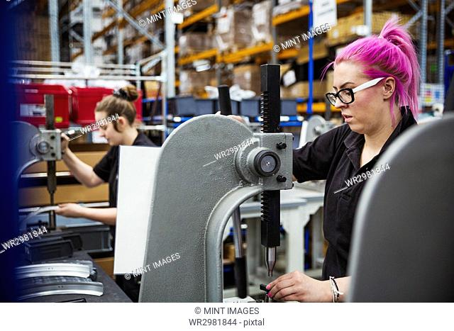 A young woman with pink hair, a female factory worker using a hole punching machine, working to assemble a bicycle in a factory