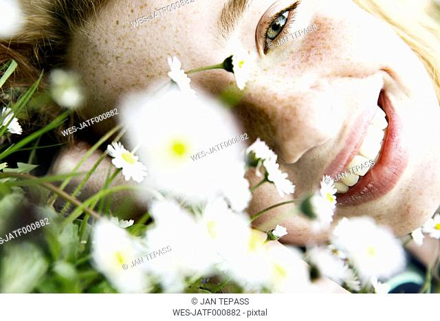 Smiling girl lying on field of flower, close-up