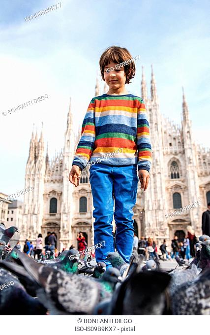 Boy amongst pigeons in Milan Cathedral square, Milan, Lombardy, Italy