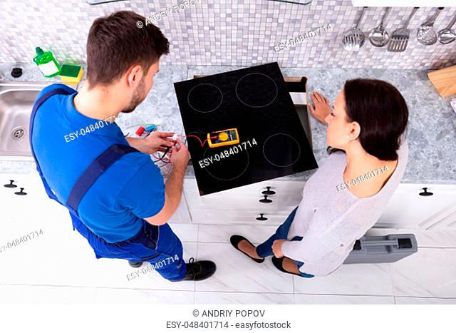 Male Repairman Installing Induction Cooker With Woman Standing In Kitchen