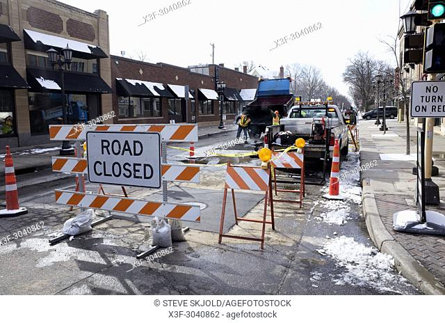 Road closed sign and striped barriers to protect workers while they fill potholes from winter damage. St Paul Minnesota MN USA