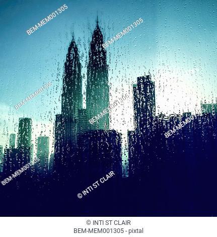 Urban skyscrapers viewed through rainy window, Kuala Lumpur, Malaysia