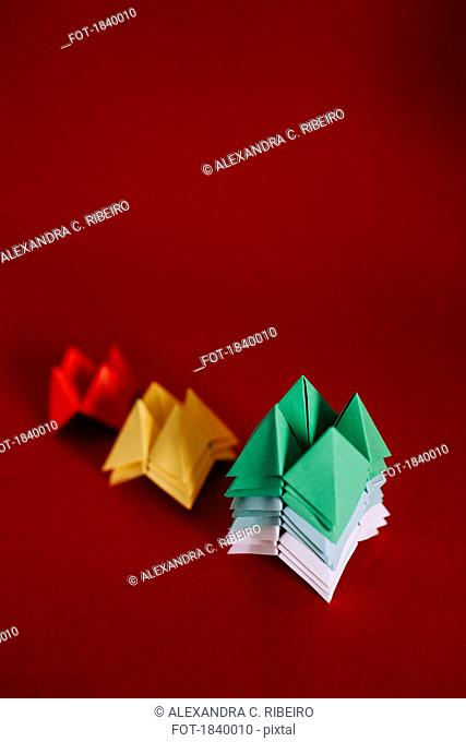 Multicolored origami fortune tellers on red background