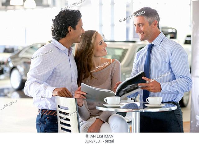 Salesman and couple looking at brochure in car dealership showroom