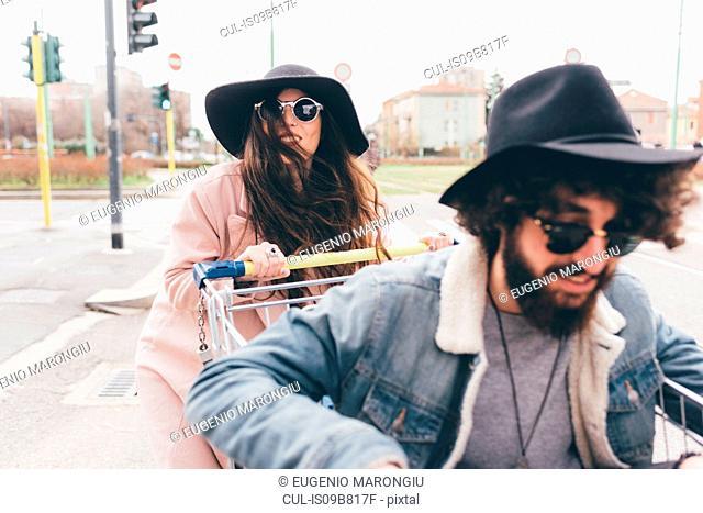 Young couple outdoors, woman pushing man along in shopping trolley