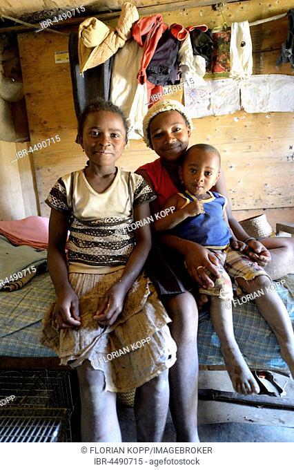 Girls, adolescents and young child in a simple hut, Ambatomainty village, Moramanga, Alaotra-Mangoro region, Madagascar