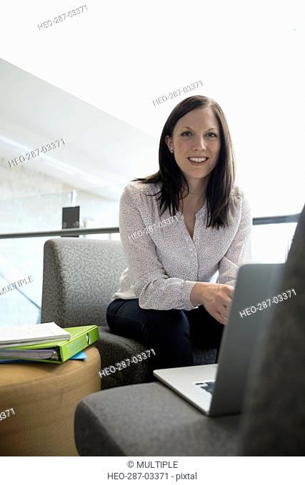 Portrait smiling adult education student using laptop