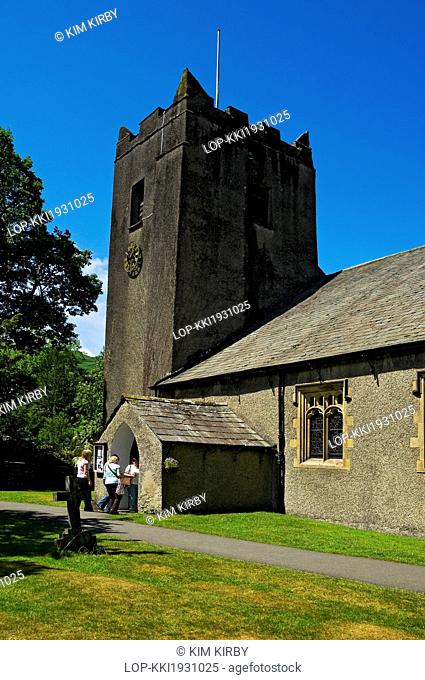 England, Cumbria, Grasmere. Visitors entering St. Oswald's Church in Grasmere. The churchyard is famous for the Wordsworth family tomb