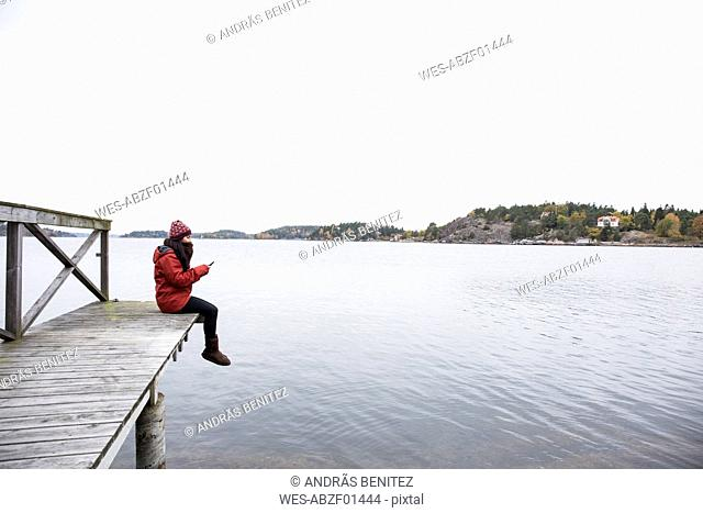Woman sitting on pier text messaging