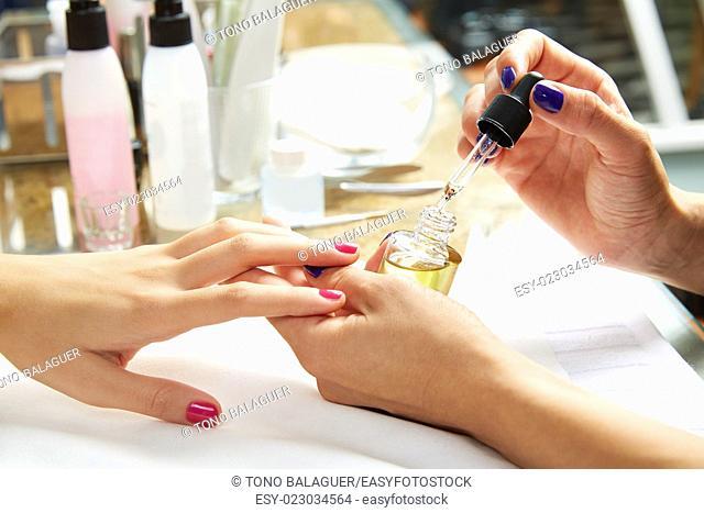 Nails top coat finishing vernis after nail polish in woman hands at salon