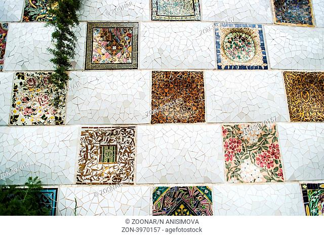 BARCELONA, SPAIN - JULY 13: The mosaic tiles wall in the park Guell, designed by Antonio Gaudi, on July 13., 2012 in Barcelona
