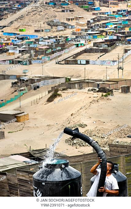 A Peruvian water distribution worker with a pipe fills a tank with drinking water on the dusty hillside of Pachacútec, a desert suburb of Lima, Peru