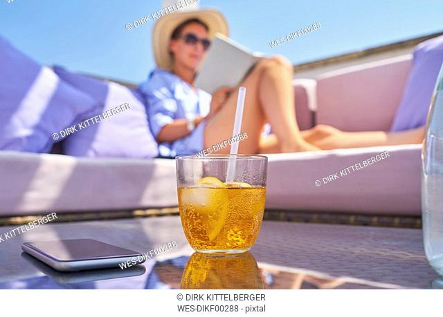 Glass of Crodino, smartphone and woman relaxing on sun deck in background